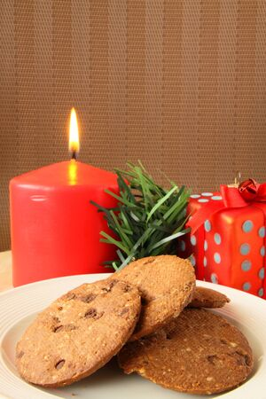 Christmas cookies serving on white plate with red candle at background