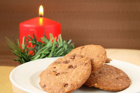 Christmas cookies serving on white plate with red candle at background Stock Photo - 11762469