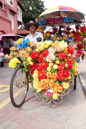 MALACCA, MALAYSIA - JANUARY 1: Heavily decorated bicycle rickshaw in Malacca City on JAN 1, 2012. The bicycle rickshaw ride is a major attraction for visitors to see the city of Malacca
