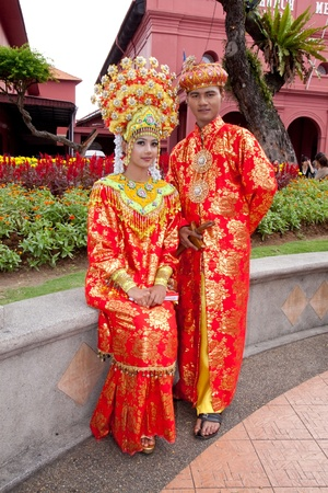 and distinctive: MALACCA, MALAYSIA - JANUARY 1: A Malay bride and groom in their traditional Malacca Malay costume on JAN 1, 2012 in MALACCA, MALAYSIA. The distinctive features of Malacca Malay matrimonial gown and accessory are the mixture of Malay and Chinese influence Editorial