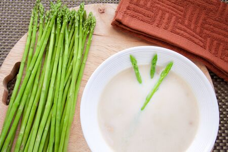 Mushroom soup with fresh asparagus on a wooden cutting board Stock Photo - 11862501