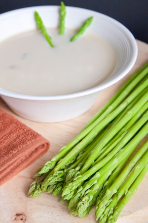 Fresh asparagus with a bowl of mushroom soup photo