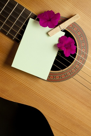 Acoustic guitar with flowers and blank card. Concept image for invitation to a romanticmusical event photo