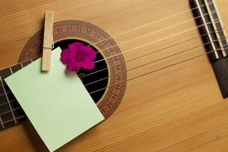 live entertainment: Acoustic guitar with flower and blank card. Concept image for invitation to a romanticmusical event Stock Photo