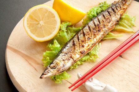 Grilled fish with lemon and red chopsticks on a wooden cutting board