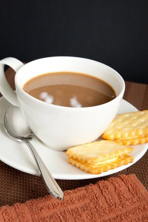 A cup of coffee with cookies and brown kitchen towel