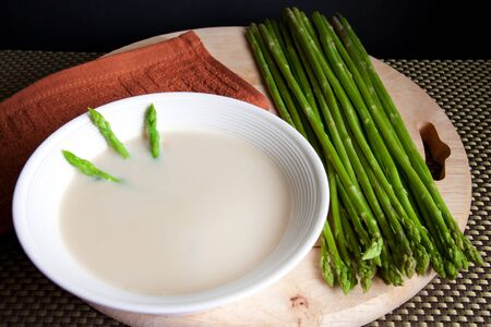 Fresh asparagus with a bowl of mushroom soup