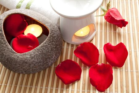 Spa Concept  Rose petals, aroma candles on bamboo mats