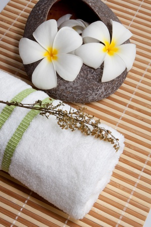 Spa Concept  Frangipani flowers, white towel on bamboo mats