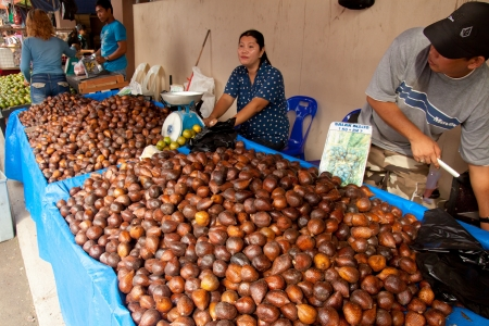 SARAWAK, MALAYSIA-JUNE 2: Woman selling Salak fruit or snake fruit at the Serikin weekend market near MalaysiaIndonesia border on June 2, 2012. Salak (Salacca zalacca) is a species of palm tree, the fruit taste is usually sweet and acidic