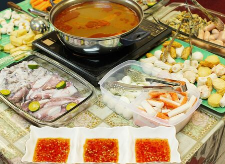 Asian dishes - tomyam steamboat set with various ingredients and spicy dipping sauce