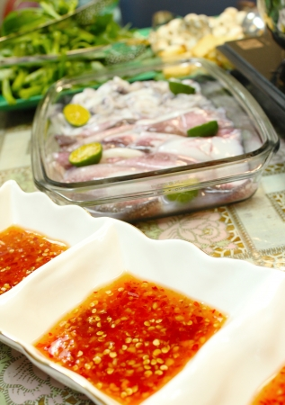 Asian dishes - spicy dipping sauce for steamboat and fresh squids set in shallow depth of field Stock Photo - 14416788