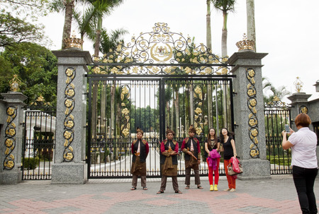 KUALA LUMPUR, MALAYSIA - FEBRUARY 17  Tourists taking photo with armed guards in traditional Malay costume at the entry gate of Royal Museum in Kuala Lumpur, Malaysia on February 17, 2013