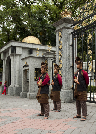 KUALA LUMPUR, MALAYSIA - FEBRUARY 17  Armed guards in traditional Malay costume stand at the entry gate of Royal Museum in Kuala Lumpur, Malaysia on February 17, 2013