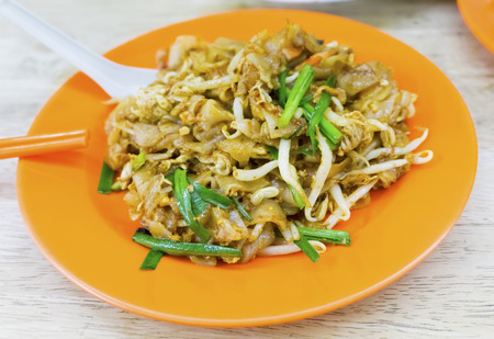 Malaysian cuisine. Char Kway Teow is a flat rice noodles stir fried together with pork lard, egg, soy sauce, bean sprouts and Chinese chives