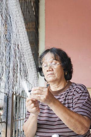 SARAWAK, MALAYSIA - SEPTEMBER 23: Unidentified Bidayuh woman mending her fishing net in Sarawak, Malaysia on September 23, 2010. Bidayuh is one of the indigenous tribes of Borneo Island Editorial