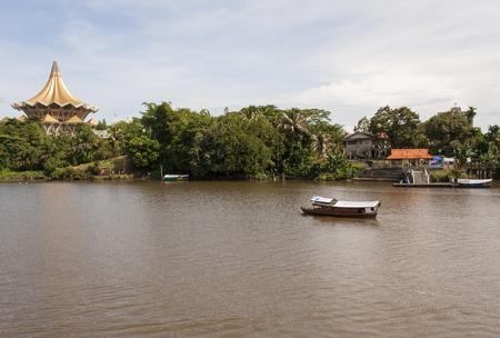 legislative: KUCHING, SARAWAK - SEPTEMBER 24: Traditional river boat transporting people across Sarawak River with State Legislative Assembly as the background on September 24, 2010 in Kuching, Sarawak, Malaysia