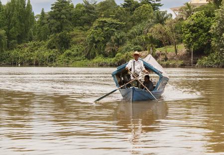 KUCHING, SARAWAK - SEPTEMBER 24: Traditional river boat transporting people across Sarawak River on September 24, 2010 in Kuching, Sarawak. This ?perahu tambang? is Kuching city famous icon Editorial
