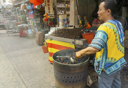 KUALA LUMPUR, MALAYSIA - January 17: Hawker roasting chestnuts in Petaling Street Chinatown on January 17, 2015 in Kuala Lumpur, Malaysia. These coffee roasted chestnuts were Petaling Street famous snack among tourists and locals Editorial
