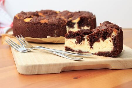 Cheesecake with chocolate shortcrust pastry and chocolate crumble arranged on a wooden board