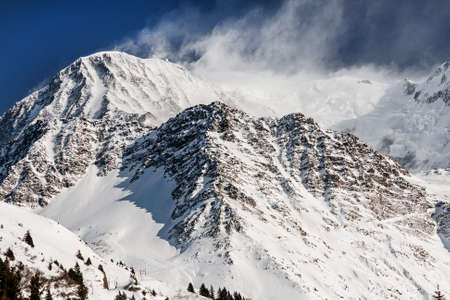 snow covered mountain: Snow covered mountain peaks blown by the wind