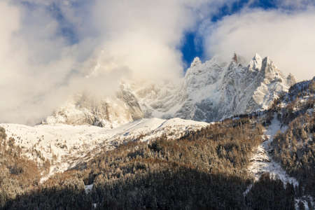 aiguille: French alps mountain summits in winter covered by snow and clouds Stock Photo
