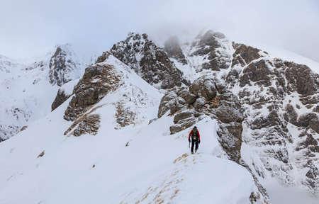 crevasse: Climber ascending snowy mountain ridge up to summit