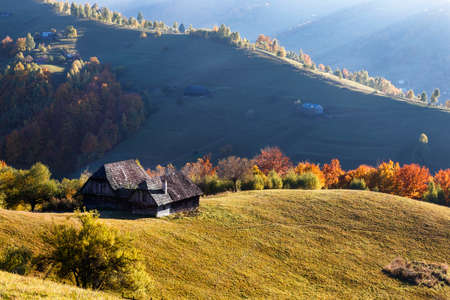 Autumn Landscape with a wooden house on the slopes of the mountains and sunshine Stock Photo