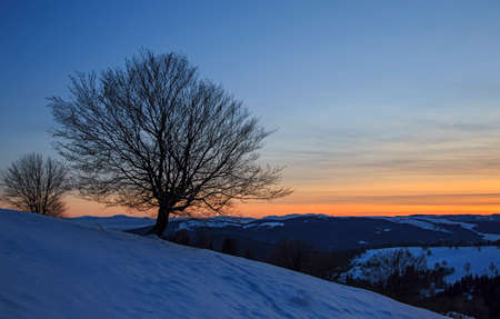 Sunset over the snowy hill in Transylvania
