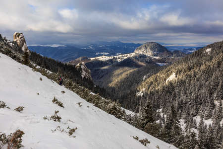 Winter mountains with snow and forests in cloudy day. Stock Photo