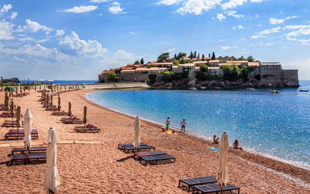 stephen: Sand beach with wooden chairs and umbrellas near the Sveti Stefan historical town on the island.