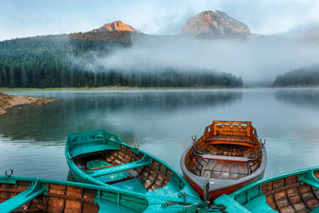 Morning landscape with mountains, lake and boat