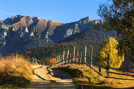 Stunning colorful autumn alpine landscape with green fields and high mountains