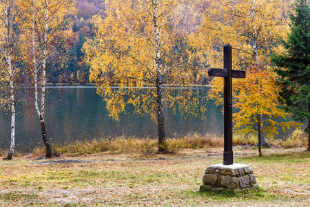 backwater: Big wooden cross at the lake in autumn