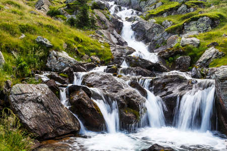 The waterfall of a mountain river with rocks in the Carpathians.