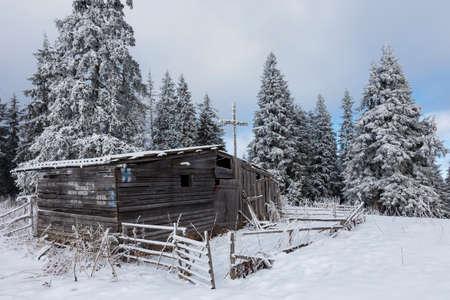 Old abandoned shepherd house in a frosty winter wonderland, Carpathians, Romania Standard-Bild