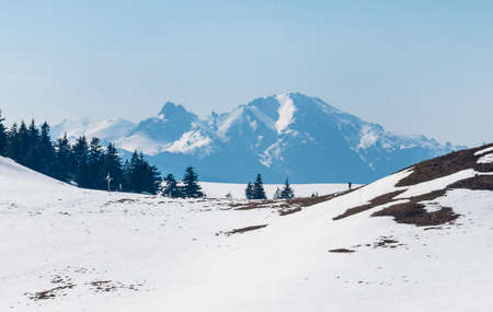 Snow covered mountain range in spring on a clear day