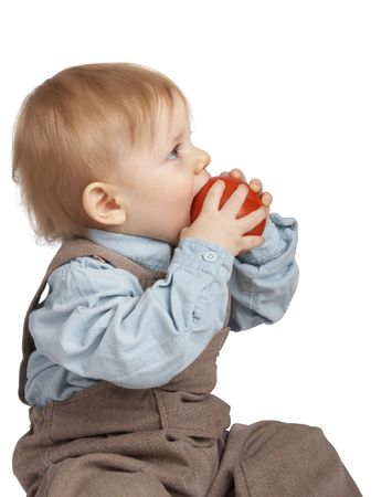 tot: One-year boy eats a tomato.