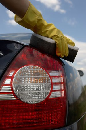 valet: hand in a yellow glove washes car Stock Photo