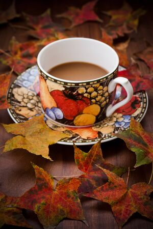 Cup of coffee with autumn leaves