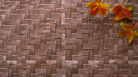 Bamboo weaving with maple leaves, use as texture background.