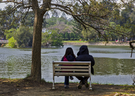 voiceless: A couple sit in water side in a city park