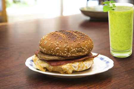 Hamburger and juice on a wood table with morning bright light.