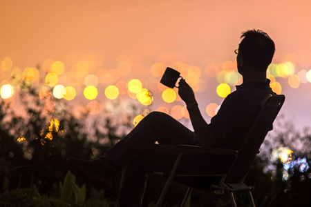 A man holding a cup and sitting on a hill with background of city night light. Stock Photo