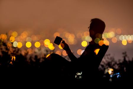 Een man met een kop en zittend op een heuvel met de achtergrond van de stad 's nachts licht.