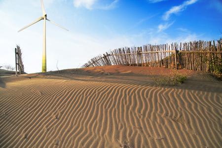 Zon van de zomertijd op hemel en zand van het strand met molen.