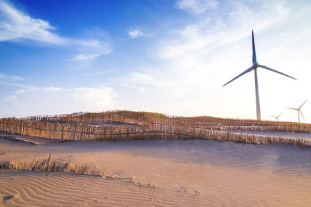 Wind mill on the sand dunes with bamboo fence Stock Photo
