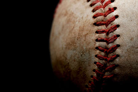 homerun: an abstract macro of a used baseball with focus on a set of stitches, shot over black