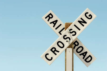 wood railroad: railroad crossing sign on wood against a clear blue sky