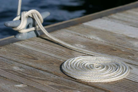 a neatly coiled rope leading to the cleat and a moored sailboat in yellowstone national park, wyoming photo